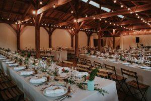 Grange De Mariage Avec Une Décoration Rustique Et Champêtre Aux Petits Vases De Fleurs Sur Des Tables Rectangulaires.