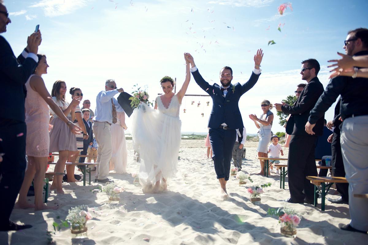 Cérémonie laïque en été d'un mariage simple et bohème avec les mariés les pieds dans le sable de la plage du Cap Ferret.