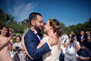 Mariés Et Couronne De Fleur Pendant Leur Cérémonie De Mariage Sur La Plage Du Cap Ferret.