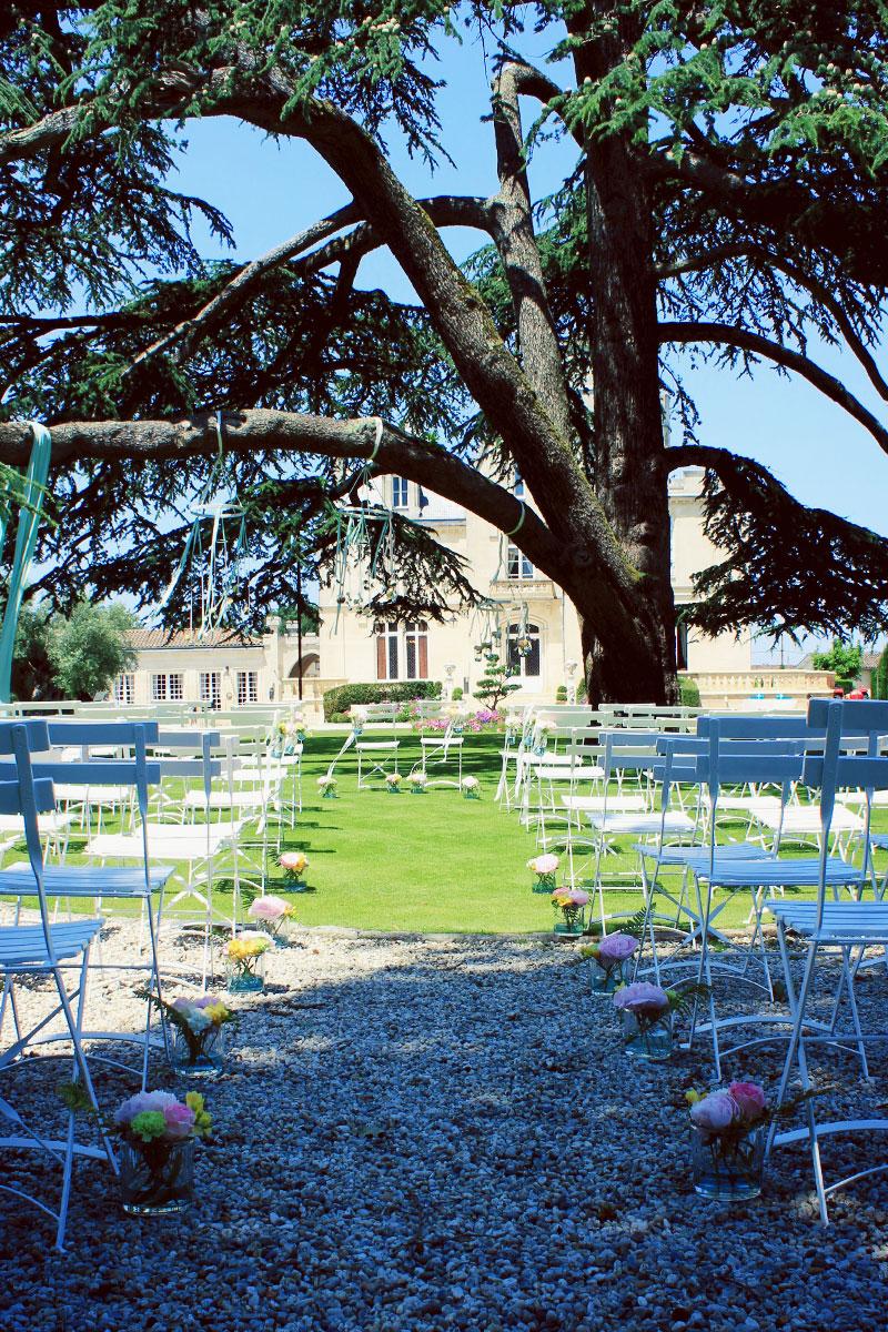 Décoration de mariage coloré et estivale avec des bouquets de fleurs de cérémonie autours d'un arbre champêtre.