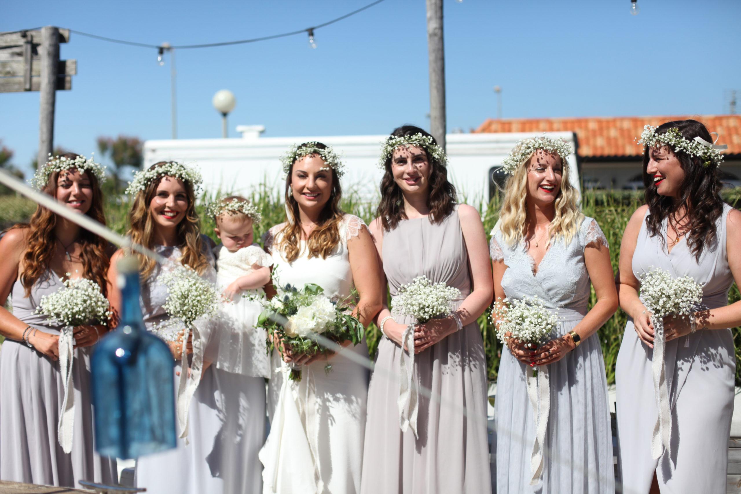 Bouquets de demoiselles d'honneur champêtre et chic où la mariée pose avec son enfant et ses témoins aux couronnes de gypsophile.