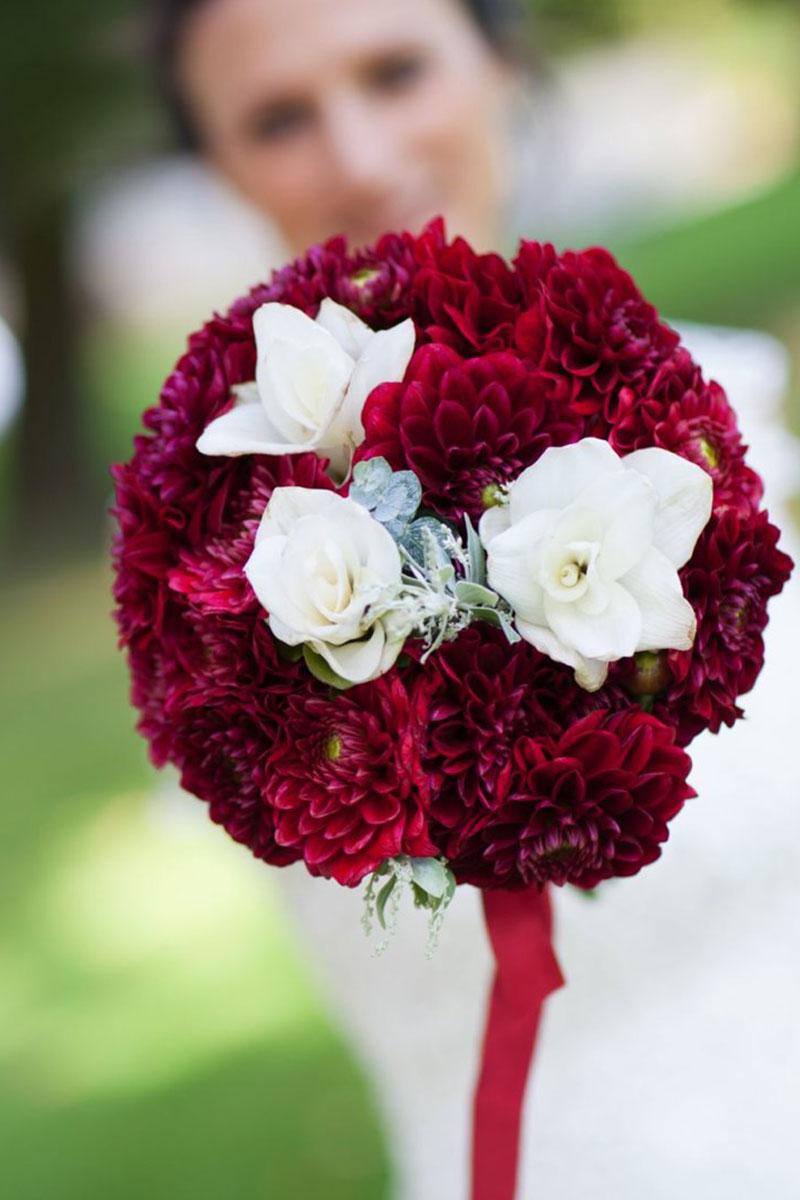 Bouquet de mariée en dahlia rouge et fleurs blanches lors de mariage romantique.