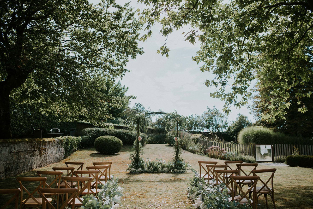Décoration mariage extérieur dans un jardin champêtre avec une arche de cérémonie aux bouquets et fleurs romantique chic.
