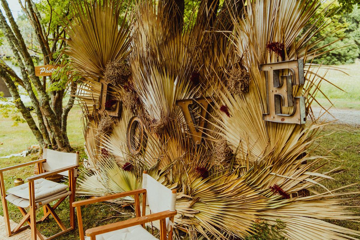 Photobooth de mariage original en fleurs séchées et feuilles de palmier pour une déco d'animation de mariage.