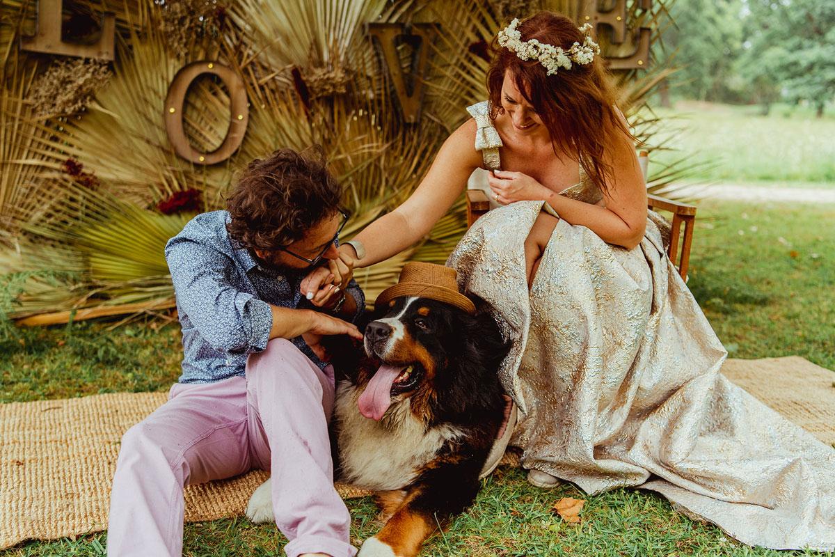 Lettre lumineuse et feuille de palmier en or forment ce photobooth de mariage chic et champêtre.