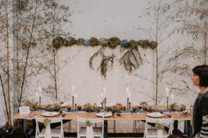 Centre De Table Avec Arche En Bambou Et Hortensia Dans Une Salle D'événement Moderne Et Industrielle.