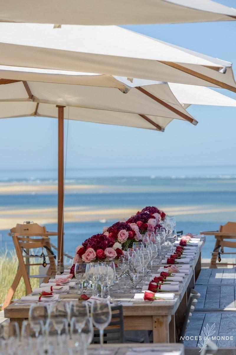 Réception romantique à la plage avec comme bouquet et centre de table une décoration romantique en fleurs de roses.