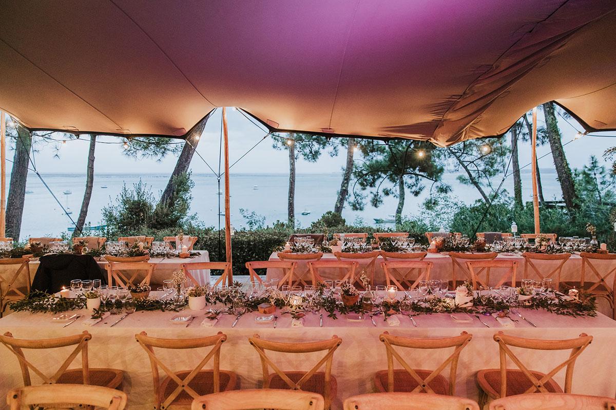 Décoration de mariage sous chapiteau en bord de mer au fleurs et bouquets champêtre bohème à la plage.