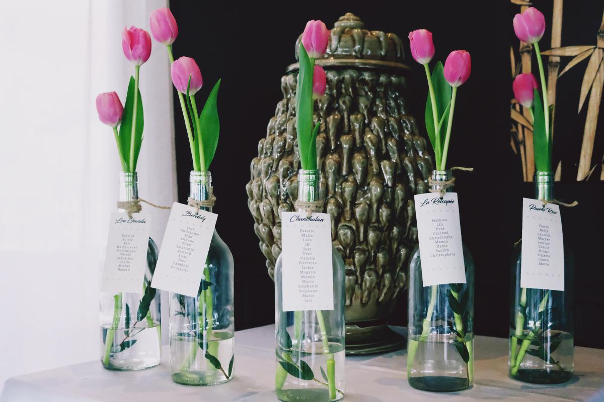 Plan de table en bouteilles de verres et tulipes pour un mariage à la Maison du Fleuve à Camblanès et Meynac.
