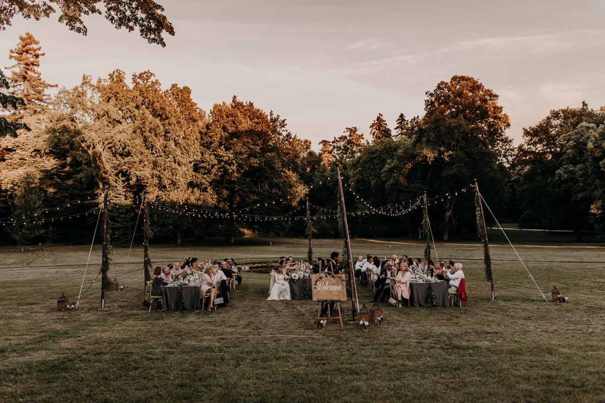 Décoration de mariage à l'américaine aux tables en extérieur avec guirlande lumineuse au thème bohème.