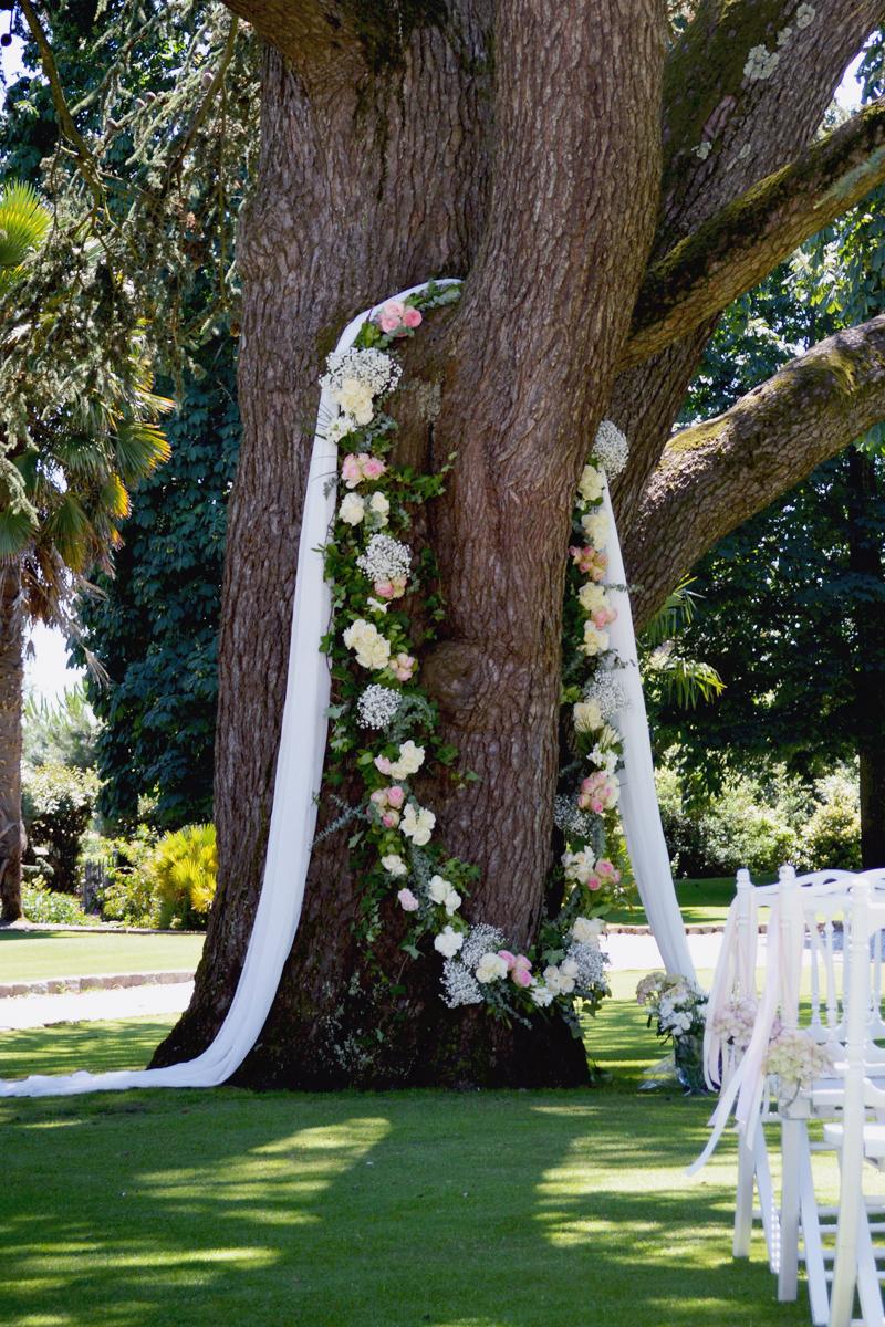 Drapé blanc pour arbre de cérémonie de mariage avec fleurs au thème champêtre chic.