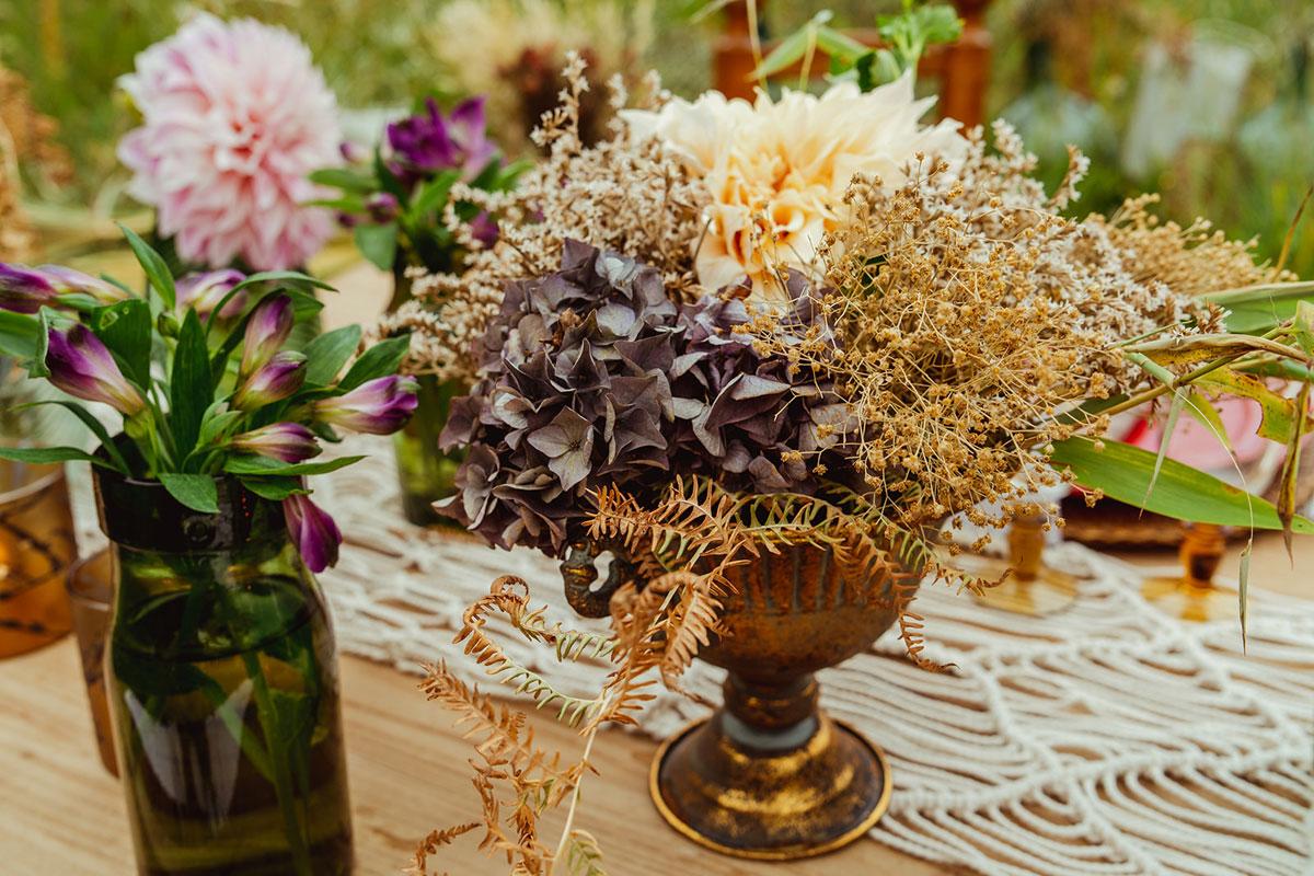 Composition florale tendance de l'année 2022 en fleurs séchées et idées de déco au thème champêtre bohème de centre de table de réception de mariage.
