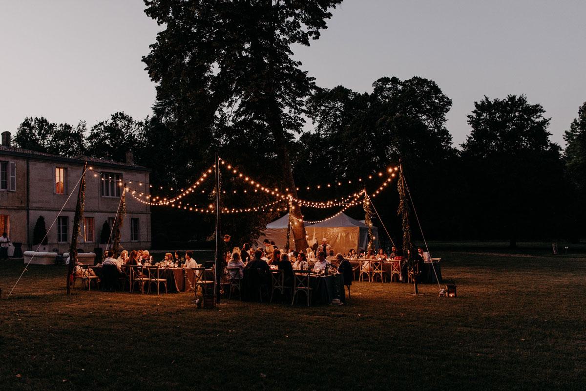 Tendance de décoration mariage 2022 en inspiration de réception en extérieur à l'atmosphère nomade et sauvage avec la guirlande lumineuse.