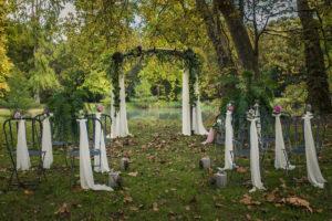 Voiles Blancs En Tissus Pour Chaises Et Arche De Cérémonie De Mariage En Extérieur Au Thème Romantique Avec Feuillage Et Bouquets De Fleurs.