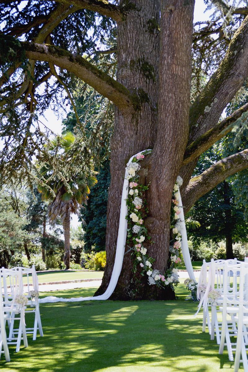 Guirlande de fleurs naturelles en déco de cérémonie de mariage en jardin et extérieur au thème bohème champêtre.