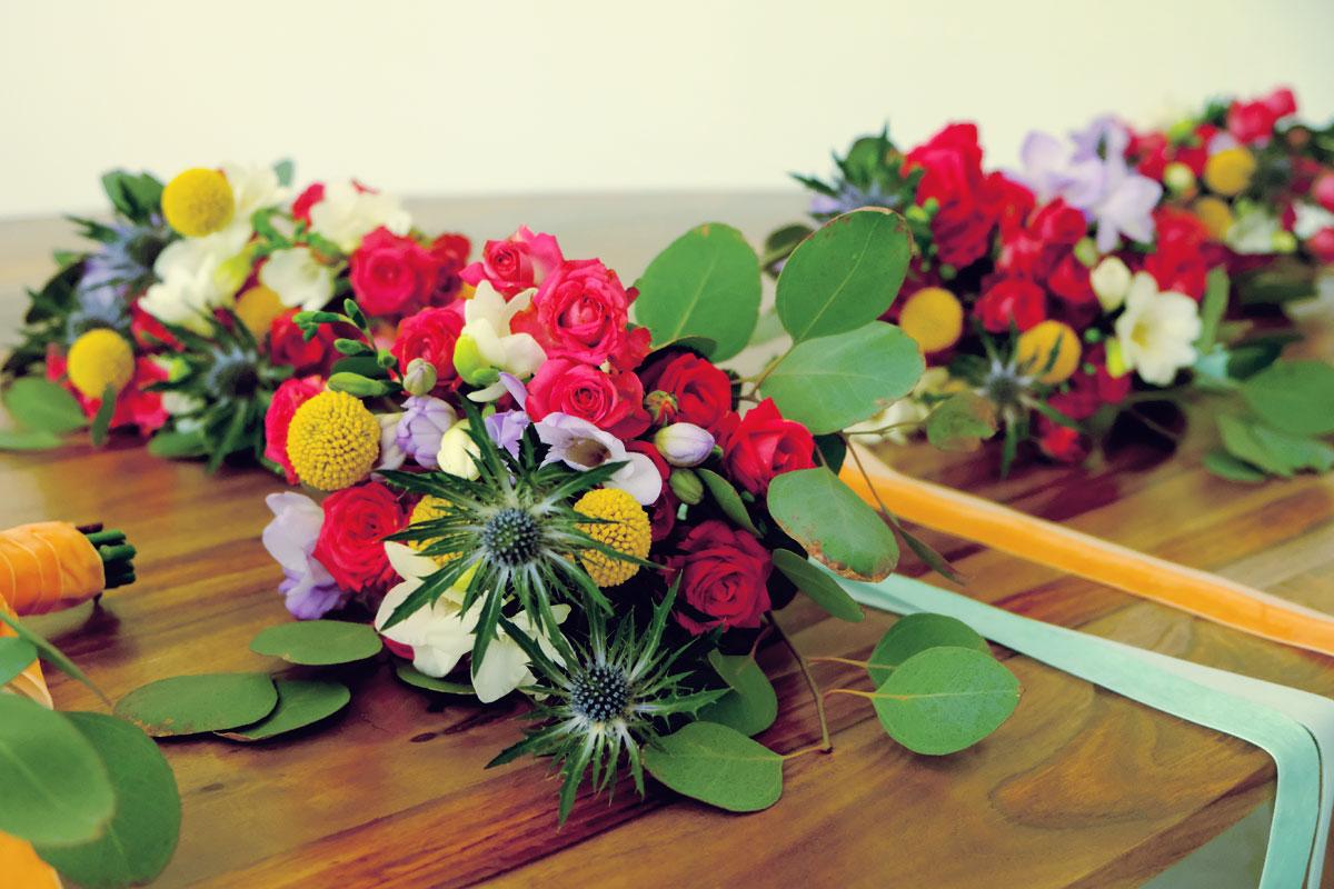 Bouquet de demoiselle d'honneur en eucalyptus et fleurs de couleur rouge et jaune.