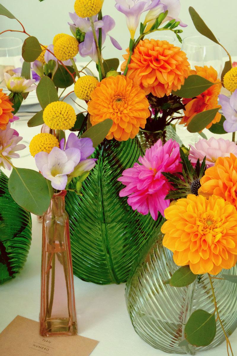 Composition florale en dahlia orange, freesia violette et crapédia jaune de mariage en été.