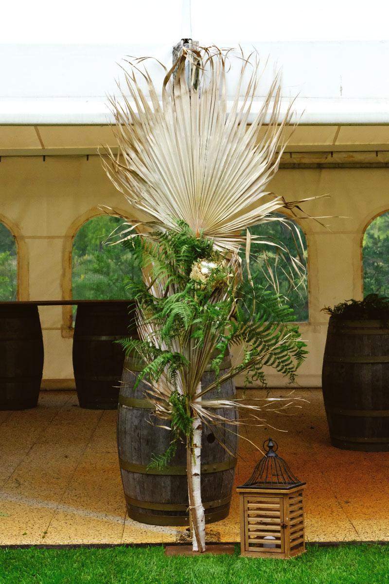 Déco bohème en feuille de palmier et fougère aux poutres du chapiteau de la ferme d'En Chon.