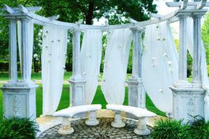 Suspension De Fleurs Au Thème Romantique Chic Avec Drapé Blanc Pour Cérémonie Laïque De Mariage Aux Colonnes à L'esprit Grèce Antique.
