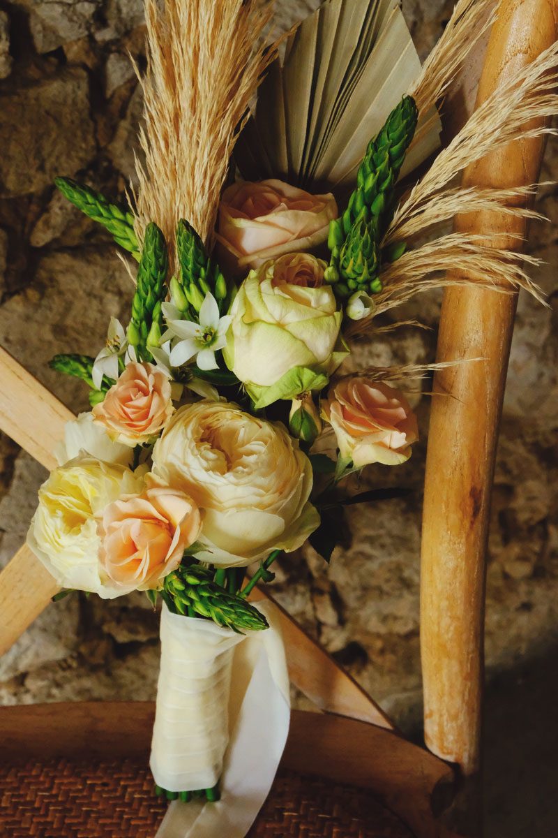 Bouquet de mariée en herbe de pampa, feuille de palmier et fleurs fraîches de mariage champêtre et bohème.